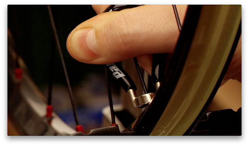 A spoke and a nipple are essentially a screw and nut that thread together to tighten and add tension to the wheel. They use standard right hand thread, but because you are looking at the nipple upside down, you have to remember to turn the spoke wrench clockwise to loosen and counter-clockwise to tighten. Only turn the wrench a small amount at each go, an 1/8th to a 1/4 turn at a time will prevent you from overdoing it and limit the damage if you do end up doing something wrong, which is likely to happen when you are learning.