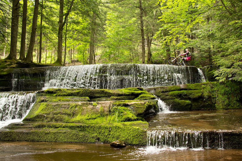 KHS Factory Rider Logan Binggeli poppin a wheelie across a set of waterfalls in New York during the 2012 Pro GRT #3 in Plattekill Mountain.