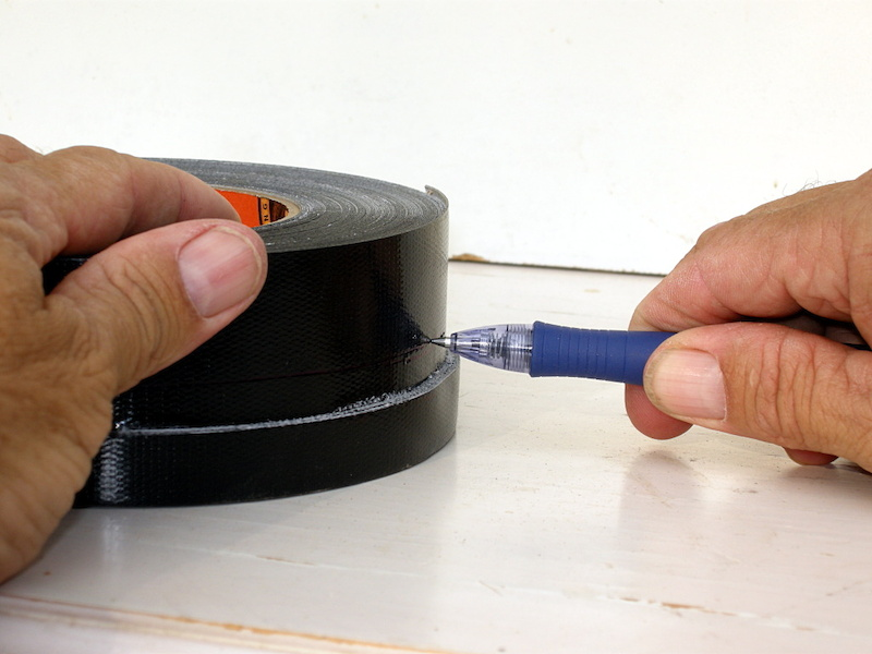 Brace the pen with your hand against a table so that the tip lines up with the mark on the tape and then spin the tape roll to mark the entire circumference.
