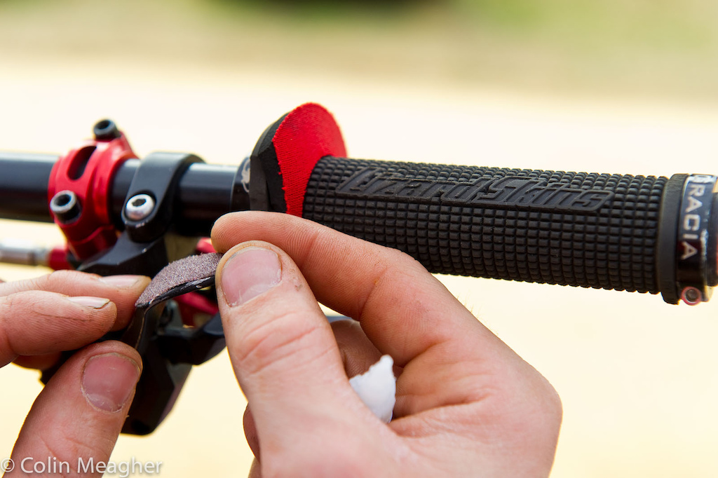 Cedric Gracia getting a little extra grip on his thumb shifter courtesy of some sandpaper and a dab of super glue.