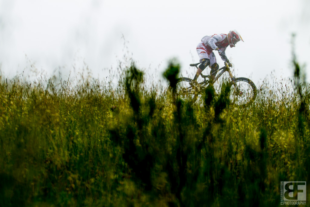 Greg Minnaar jumps his way through the tick infested grasses lining the downhill track.