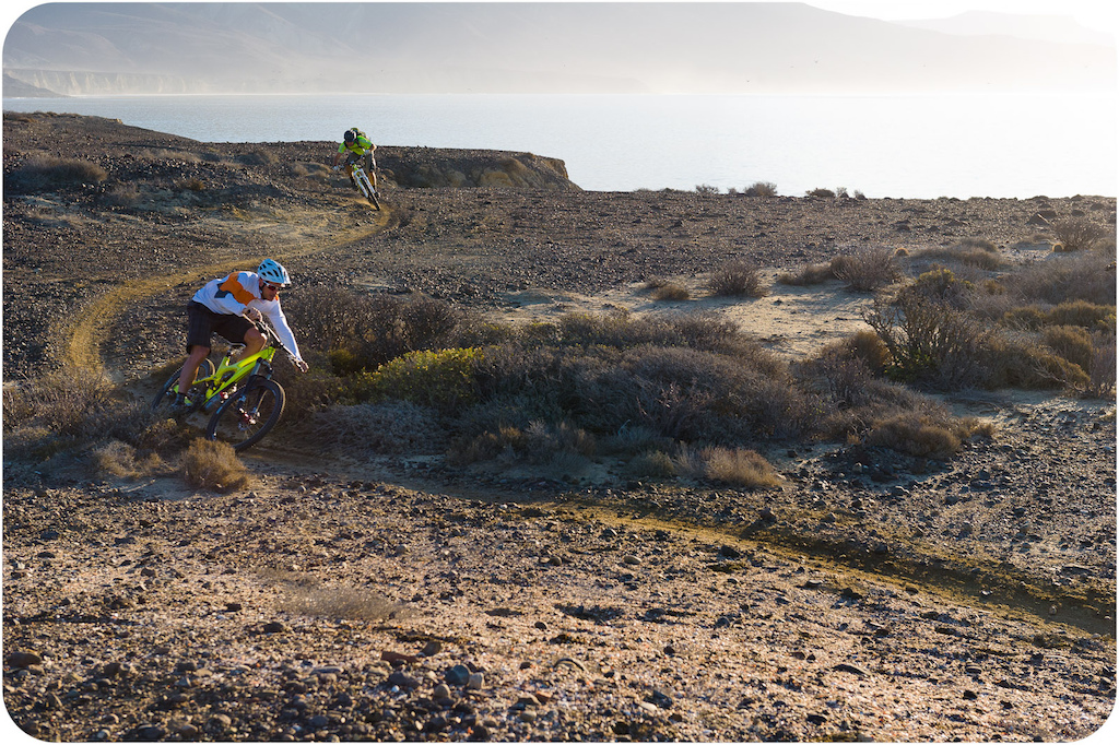 Brian Lopes and Richie Schley ride along the coastline trail at Punta San Carlos in early morning light.