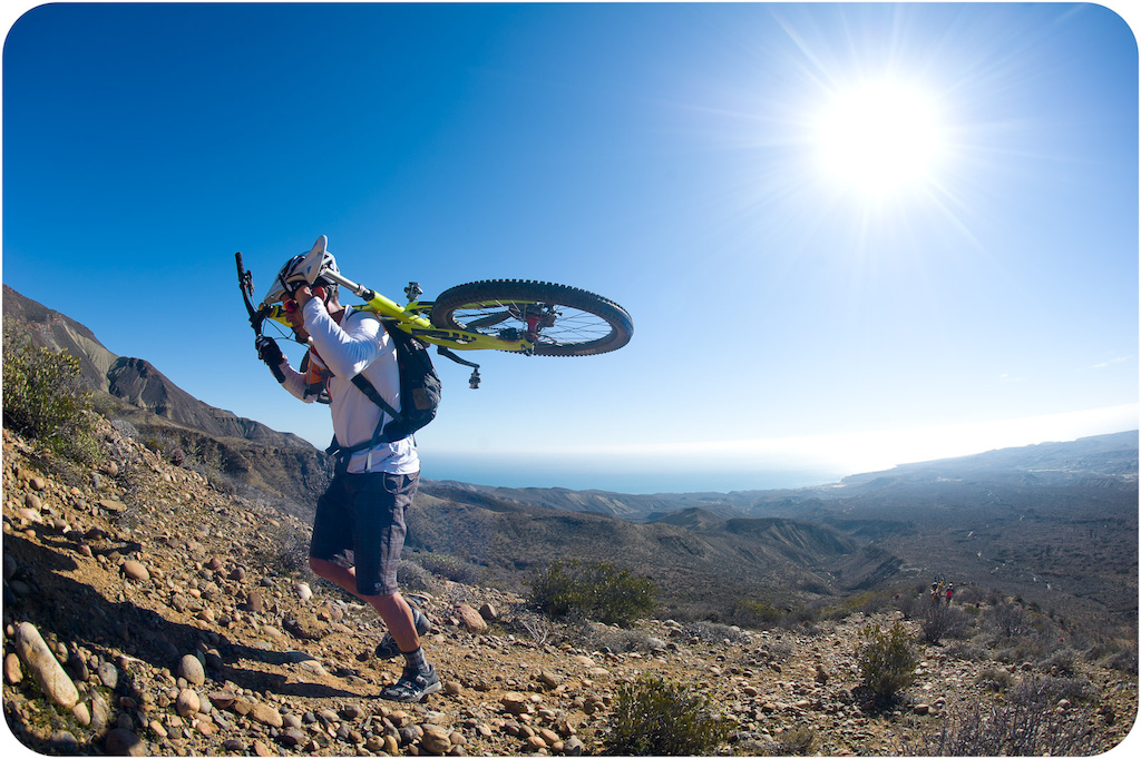 Brian Lopes carries his bike up the long trail to the top of the mesa at Punta San Carlos.