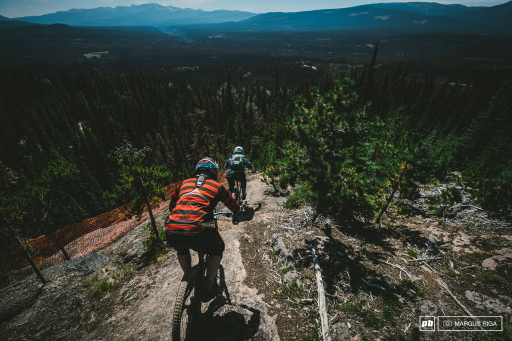 Liam Baker follows Meg Broswick. See that orange fencing Exposure. BC big mountain riding.