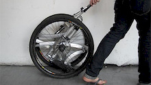Inventor's bike folds into its own wheel!