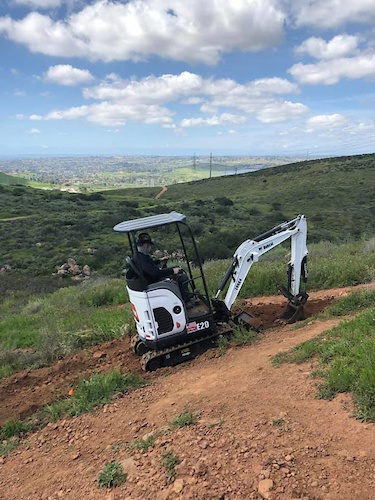 SDMBA mini excavator getting tread ready for volunteers to finish by hand.
