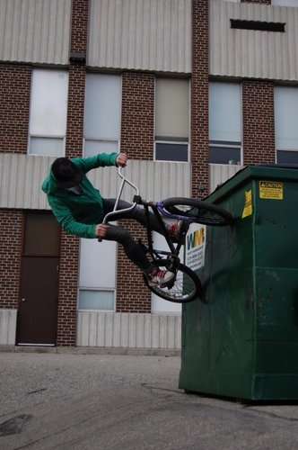 Adam wall riding a dumpster