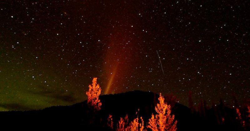 We camped at the Racing River - red glow of a campfire red pink green aurora and a shooting star