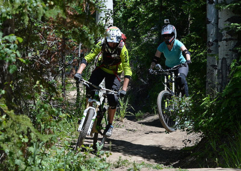Nicole Miller follows Steamboat Bike Park instructor Andrew Burns tips as she navigates turns on the Wrangler Gulch trail.