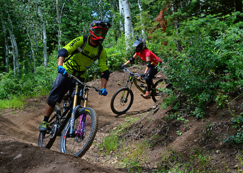 Steamboat Bike Park instructor Tim Price leads Nicole Miller through a banked turn on Rustler Ridge a blue downhill trail in the Steamboat Bike Park.