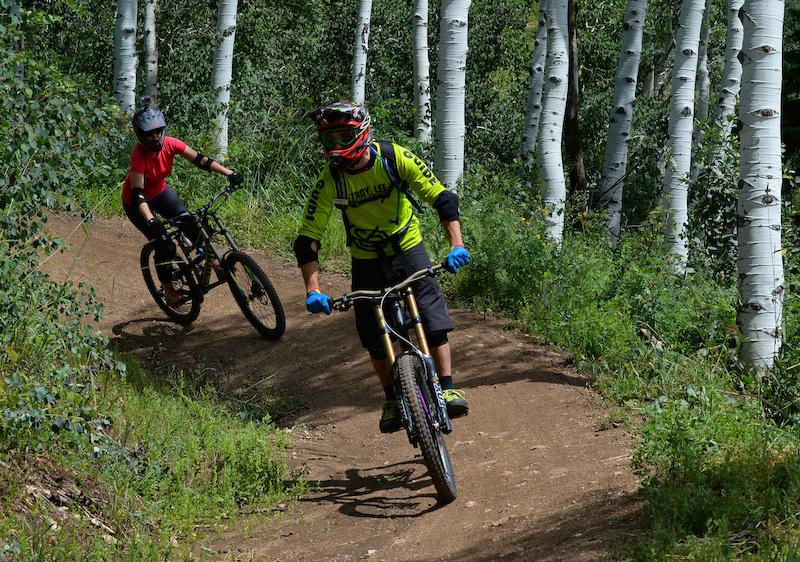 Nicole Miller follows Steamboat Bike Park instructor Tim Price on Rustler Ridge a blue downhill trail in the Steamboat Bike Park.