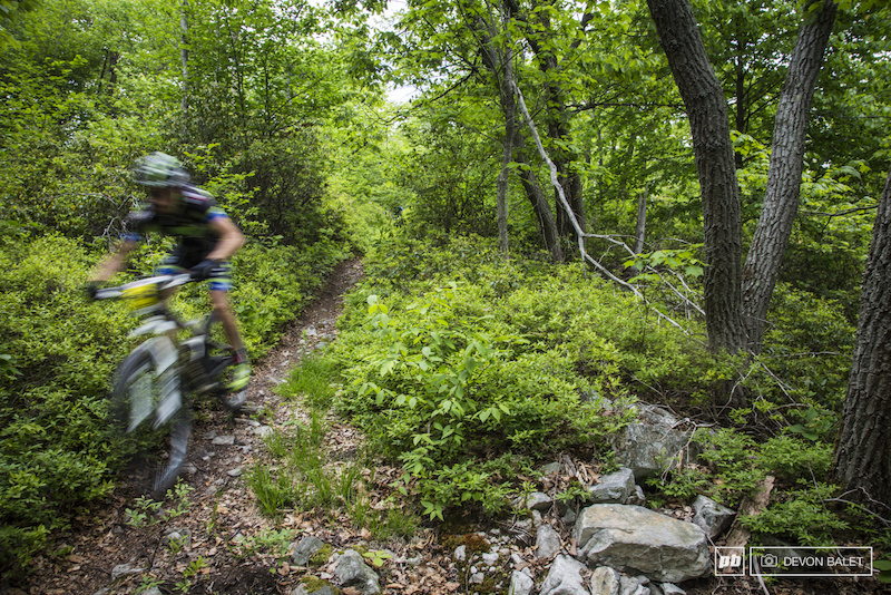 A racer blurs through a buff section of stage three. High speeds on smooth trails will quickly open up to rocky square edged rocky trail.