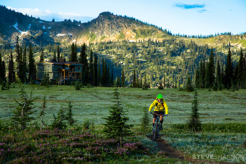 A mountain biker enjoys pristine alpine singletrack right out the door of the lodge at Sol Mountain Lodge in the Monashee mountains near Revelstoke British Columbia.