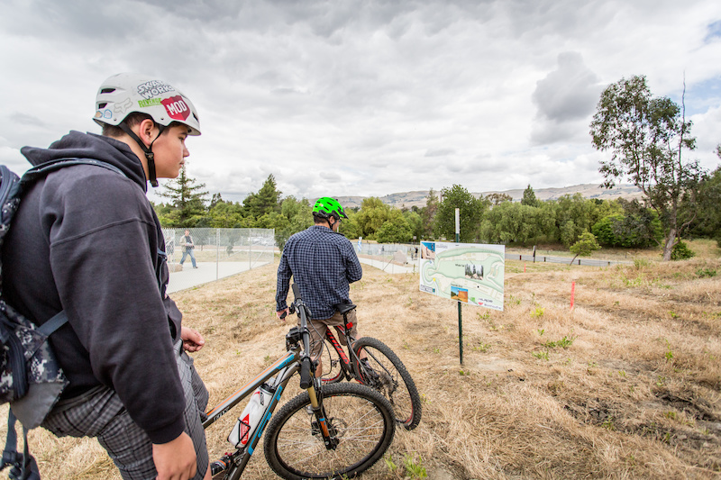 A couple of bike riders look over the plan board for the Slopestyle Course. The course will feature several wood features including a Whale Tail and four wall rides with berms near 10 feet high according to Justin Beck.