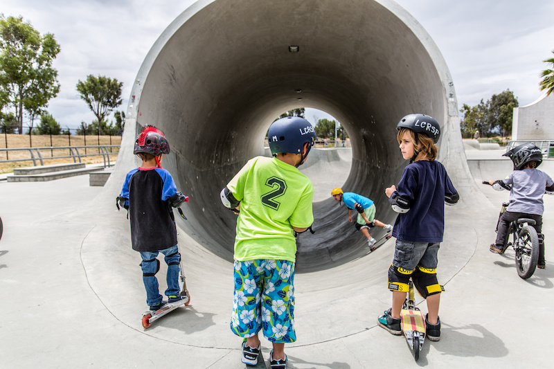 Little groms watch as a vet skater rides the world s largest full pipe unofficially .