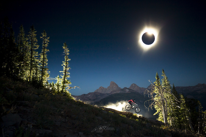 Chris Brule charges off a natural feature underneath the Grand Teton on the Total Solar Eclipse, August 21st in Teton Valley, Wyoming.