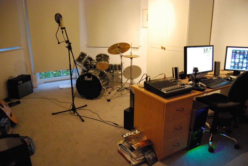My Computer & Studio. Since the pics were taken I have added a Yamaha PSR-K1 Keyboard (in place of the wardrobe), a KORG MiniKORG Synthesizer w/vocorder microphone (between 2nd screen and printer), and 2 Behringer C2 overhead mics for the drums.