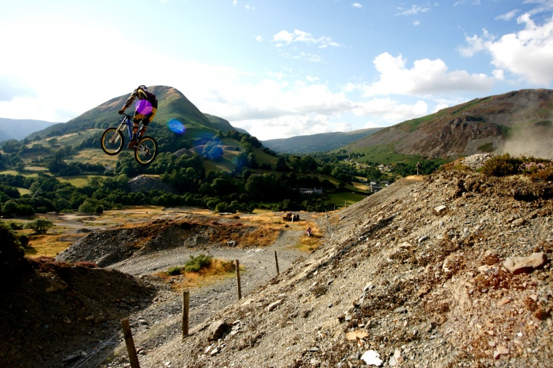 Old shot of Gee on virgin hit of huge huck near his home in Wales. He lands over the ridge at the bottom left of shot.