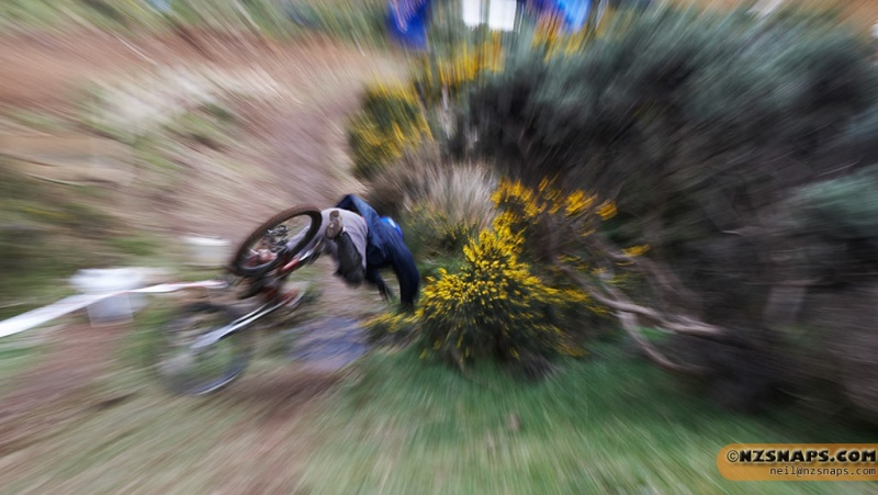 2009 AKDH round at Long Gulley in Wellington. This poor guy crashed into a gorse bush. I had the camera setup for a panning shot and heard the crash start. With the camera at my hip, I turned - holding the shutter button down. I also accidentally zoomed while shooting. There is NO PHOTOSHOP in this image!