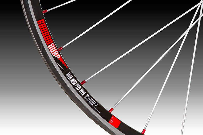 The cherry atop the cake has to be DT's extravagant EX 1550 wheels. These hoops are unashamedly over the top: while DT's high-end hubs and spokes certainly play a big part in the story of the EXC 1550's, the real story here is the use of carbon for the rim material. The handmade carbon rim uses a unidirectional (UD) material as opposed to a 3K carbon weave that you may be more used to seeing. That is why the rims do not have the classic carbon look and at first glance look more metallic than anything else. By choosing to use UD carbon instead of a more classic looking weave, DT has managed to shave unneeded grams while still retaining carbon's inherent strength. They also kiboshed the idea of throwing on a cosmetic-only layer of carbon weave to achieve the expensive look that some people may prefer. It's all about the grams here folks, nothing extra that isn't going to make the EXC's lighter or stronger. Taking advantage of carbon's inherent strength, DT has built a vertical rib within the rim that should not only produce a laterally stiffer rim, but also an added amount of vertical strength. The use of carbon, along with the technique used to manufacture the rim itself, allows the final product to be not only incredibly light, but it should also be quite a bit sturdier than its aluminum counterparts. There are quite a few wheelsets out there that are in the same weight category, but nearly none of those can vouch for having the same 29 mm width that works so well with the larger, high volume AM tires that a lot of riders are using. Those wide tires on an equally light, but much skinnier rim, will not have enough support to keep them from folding over on themselves at optimum pressures. There are aluminum options with similar widths that approach the EXC's 400 gram rim weight (a Stan's Flow rim comes in at about 450 grams), but DT would say that their carbon rim is considerably stiffer and stronger in all regards. At the center of the wheels you'll find DT Swiss's o