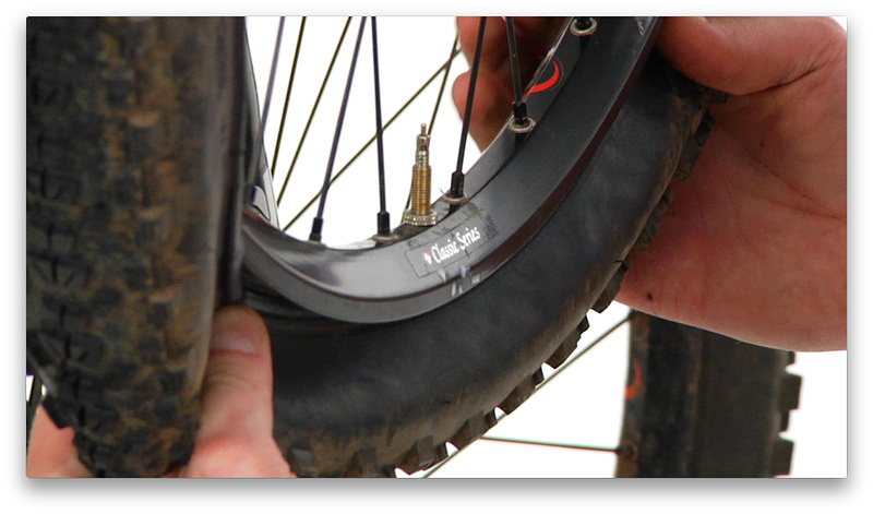 2:48 mark - Keeping the wheel in the same position (valve stem at 6 o'clock), use both hands to install the bead evenly around the tire, finishing at the 12 o'clock position