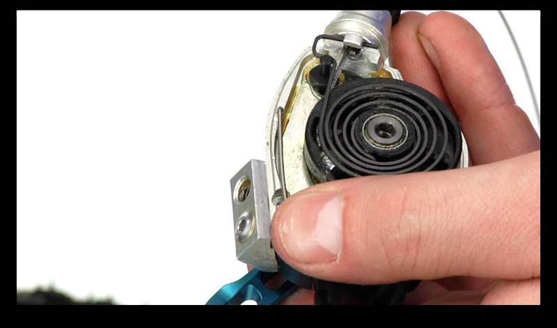 Step 4. With the cover off you should be able to spot the end of the cable just underneath the large spring. Take note of where it sits and the path that it takes to exit the shifter. You should be able to dislodge the head of the cable by gently pushing the cable into the shifter through the barrel adjuster. Completely remove it from the shifter.