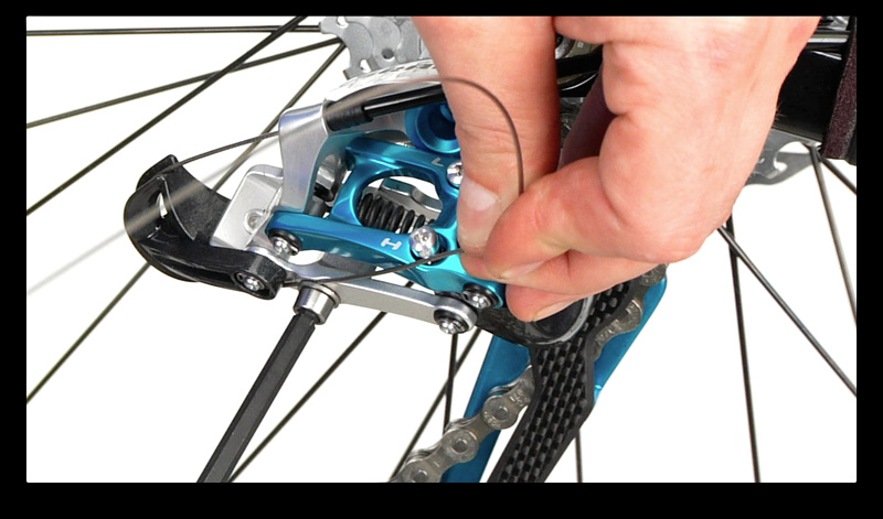 Step 10. With the derailleur still inline with the smallest cog (hardest gear), guide the cable though the correct path and tighten the anchor bolt as you pull the new cable snug