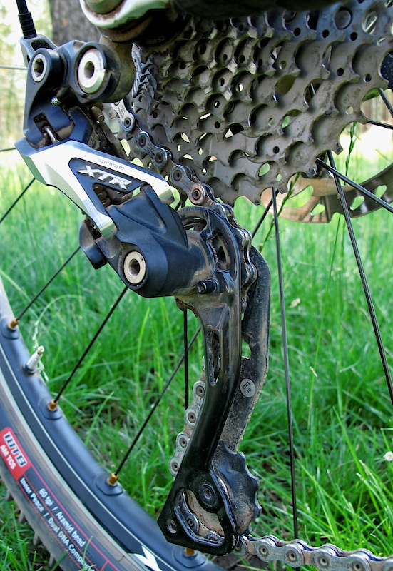 The new 10 speed XTR derailleur uses revised A-arm geometry that results in less cable tension being required for a lighter feel and less sensitivity, as well as reducing the chance of skipping as you pedal over rough terrain. The outer cage is carbon, the inner is aluminum