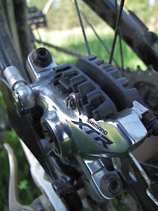 Shimano's new XTR caliper is used on both the Trail and Race systems and hides two full ceramic pistons. The two black objects atop the caliper act as cooling fins that dissipate heat via their increased surface are. They are actually attached to the Ice Tech pads, not the caliper itself. An aluminum banjo bolt is used to attach the hose to the caliper.