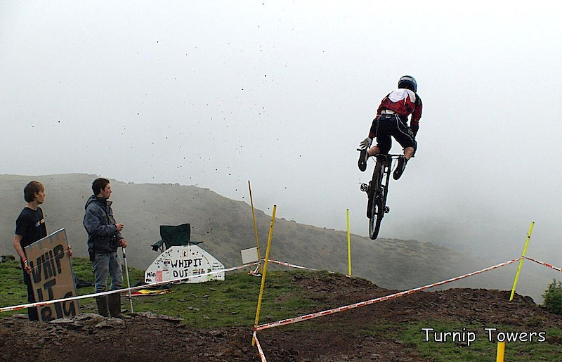 I thought this new jump near the top at Moelfre Hall might look quite spectacular with the misty background. I was hoping for a shot of a rider doing a big whip, but the jump was kicking back wheels up and causing lots of nose landings. Then Alun Lewis came down, shot straight up in the air, struggled out of his clips, did a big star jump over the bars and disappeared over the edge of the hill. I was so shocked I forgot the first rule of photography - keep shooting! I really thought he would be in bad shape, but he pushed back up the track a couple of minutes later. Although I missed what could have been a good sequence, I like the fact that I managed to catch the moment when everything is going wrong and me, the spectators and the rider are just waiting to see what happens next.