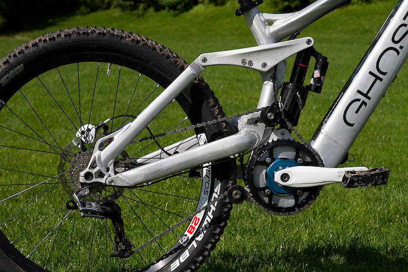 This is not an electric bike that you can ride on trails, but rather a full on mountain bike that has an electric motor - if you've seen past attempts at most electric mountain bikes you'll know what I'm getting at. The rear suspension design and components are actually the very same as Ghost uses on their new DH race bike, albeit with a slightly shorter stroke damper. They employ a high main pivot that results in a axle path that has a more rearward element than if they had placed the pivot in a more conventional location. Because it is so high they bolt on a chain idler to keep chain tension and growth in check. Have you spotted the battery yet?