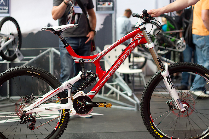 I had a long day of work before the time came to make my way over to the Santa Cruz booth to see my intended prey, the new carbon V10. If you think that she looks good in the photo, you should really give it a proper look in person - simply stunning. Right away the bike gives the impression that there is nothing extra, just the material needed to make it one of the fastest bikes on the hill. It is both lighter and more adjustable than the aluminum version that it replaces. That's right, no more aluminum V10 for next season, but don't panic too much, frame price will be similar to what the alloy model was offered at and will also include the Cane Creek AngleSet headset that it will ship with from Santa Cruz. Expect the shipping date to be around the coming December, just in time for Christmas. Have you been naughty or nice? Press play and let Santa Cruz's Josh Kissner tell you the details.