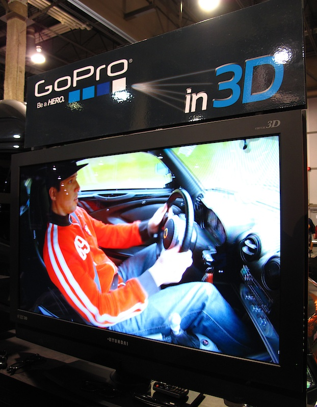 Part of GoPro's booth included a DVD loop of footage collected from their new 3D setup. The 3D Hero Housing fits two of the 1080p cameras side-by-side which feed together using a sync cable kit. GoPro has slated the unit for release early next year.