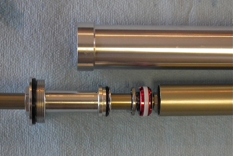 This is the anodized rebound piston inside the Vengeance. The spring loaded shim at the left side (top) of the piston acts as the check valve, with the shims on the opposite side controlling the high speed rebound stroke. The large threaded top cap on the far left seals the damping oil within the silver outer tube.