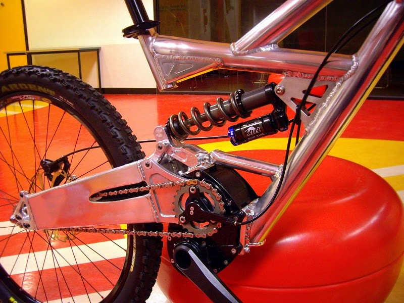 The driveside view of the Jezken makes it look more MotoGP and motocross than mountain bike. Have a look at how the chain passes through the massive swingarm on its way to the rear hub. Although it looks like it would make a fair bit of noise, it is taut and doesn't slap the swingarm at all. The bike is said to be incredibly silent. Pivoting rear dropouts allow the chain to be tensioned by loosening the three bolts and rotating the entire unit back.
