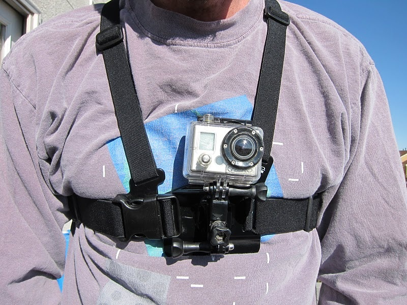 The standard GoPro chest mount - $ 39.99.  These have the extra arms that come with the HD Helmet Hero on the chest mount built as an extension (photo from gramslightbikes.com). The chest mount shows the hands, stem and wheel of the rider.  The helmet mount shows a portion of the helmet and doesn't show the bike unless you point it down, which usually means you don't get to see all of the trail in front of you.   The chest mount involves the person watching the video as you get the POV of the person filming.  The helmet mount tends to remove you from the action.  What mount you prefer is subjective to personal preference.