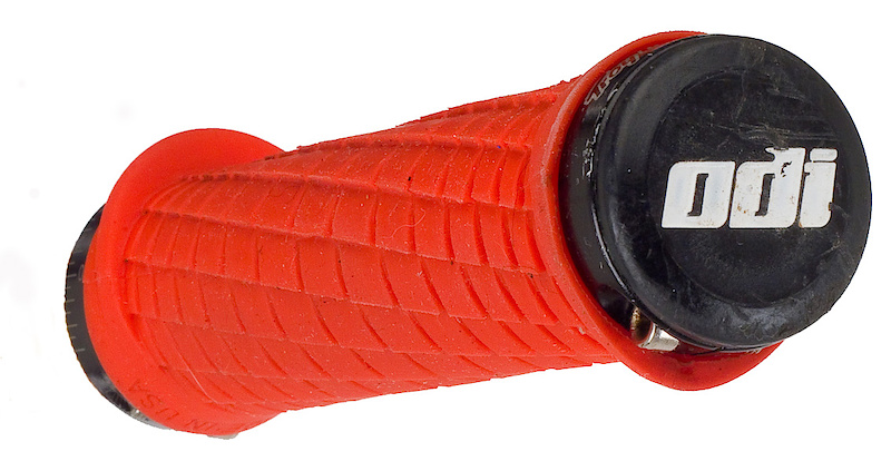 <span style='font-size:16px'>The ODI Troy Lee Signature grips use a hard compound and an aggressive design - those who don't wear gloves should beware</span> <br><br>There was a time when ODI's Lock-On grips were the only real option when you wanted to guarantee yourself no throttle grip, but now the market is flooded with various options, many that use only a single clamp on the inboard end to hold them in place. I've gone this route in the past because I've found that the outside of my palm chafes on ODI's outer clamp, but the low ramped flange on the ODI Troy Lee grips do a great job of eliminating this issue. The opposite flange on the inboard side seemed to be completely useless to me, but at the same time it isn't large enough to obstruct shifting in any way. Grip feel is very positive. There are no two ways about it, the ODI Troy Lee grips offer an incredible amount of traction between your gloved palm and the grip surface. Enough in fact, that I would never recommend these grips to any glove-less riders out there. The aggressive reverse waffle cut uses ramped leading edges combined with square trailing edges to provide a very positive feel in your hands. Now, I can't remember ever slipping a grip in the past, even in the nastiest of conditions, but it certainly feels as if there is more purchase available from these unique grips and that can't be a bad thing. They are on the thin side, measuring just 29.7 mm across with the digital calipers (RaceFace Strafe Lock-On grips come in at 33 mm, the very thin Senus non-locking at 27 mm), so those with bigger paws may want to look elsewhere. I wear a medium glove and have always preferred a thinner feel so I was right at home using the ODI/TLD grips. Wear rate looks to be impressive, with the grips pictured having well over one hundred rides on them and still looking great. It's also worth mentioning that no play developed between the aluminum clamping collars and plastic grip barrel, something that I've experienced with many other Lock-On options. Colored grips don't make a lot of sense to me, but both the red version shown here and the bright yellow versions on my bike clean up quick and look like new without too much fuss.<br><br>The ODI Troy Lee grips are great, but just like anything else, they won't be everyone's cup of tea. As mentioned above the grip pattern works well, but is very abrasive. If you don't wear gloves, these are not for you. It may sound completely silly, but they do not come with concise mounting instructions that tell you which orientation to put them on. This normally wouldn't be an issue, but running the grips in reverse produces a feeling that I would liken to giving a cactus a firm squeeze - not good. Do yourself a favor and install them with the logos facing forward. Besides those quibbles, ODI and Troy Lee Designs have put together a grip that is actually quite different from most other offerings. If you're looking for a thin, but aggressive grips, these may be just the ticket.