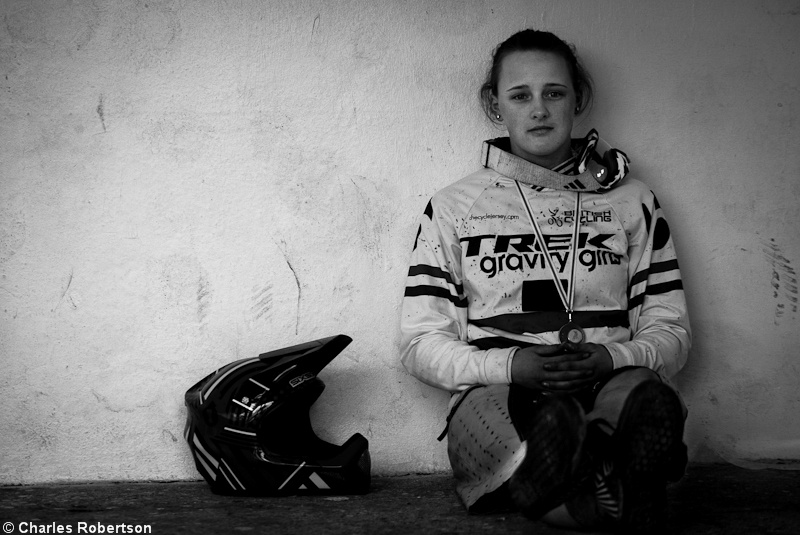 Shot 6, Another portrait this time of winner Jess Stone. This shot was set up directly behind the podium on the stage. Whilst waiting for the podium to go ahead I noticed somebody sitting on the floor against the wall and thought it would look sick in black and white. After the podium I asked Jess to grab her helmet and to place it beside her. I shot it so Jess was on a line of thirds and the helmet was on an intersection of thirds. Jess was asked to look strait past me as I don't like portraits when the subject is looking into the lens. F2.8 was the aperture as I only wanted the upper half of Jess' body and the helmet in focus. The SS was 1/640th because I wanted to freeze everything and wanted no movement what so ever. The reason for this shot was Jess won and I needed a portrait, it was posted in black and white as that is how I envisioned it