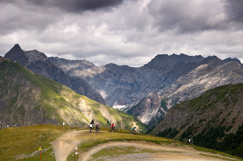 A group of riders discuss the trails near the top of the Livigno bikepark