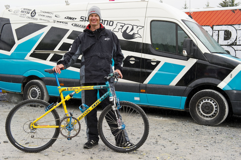 Myles Rockwell with a replica re-build of his old Mammoth Mountain Kamikaze DH bike that was on dislpay at Fort William. The front end was a glorified version of the Manitou 1 as it was called the Manitou 2. The travel was an honest 3 of unrestricted non dampened rubber grommet pogo stick bull ride travel. The rubbers would frequently explode into bits and change things mid run. The obvious other attributes are to be honest the direct cross over of cross country parts. We ran 100 the same equipment apart from possibly the wheels but that may be it as the cross country bikes. Ti spindles 23 bars Paper thin Yeti Fro IRC tires. I might ad that at the time I was running 55 to 60 psi in order to make it down the hill without pinching. I am confident that that bike has gone over 60 on dirt at the Kamikaze and Reebok Eliminator.I won 5 000 cash. You Tube Rockwell vs. McRoy I also made my first European appearance on that machine in Kaprun Austria.Three chain rings for all around riding. We fitted a Manitou bumper inside the front derailier as a fix to losing the chain. No back pedaling in those days. Rim brakes with brake boosters for stopping quick ha.
