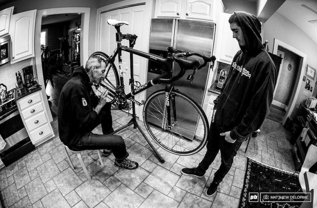 Cycling is ingrained in the Shaw family. Doug Shaw works on his cyclocross bike in the kitchen while Luca catches up on plans for the day.