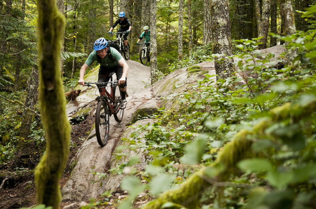 I m not sure exactly what the Squamish locals call this section of Entrails but I m pretty sure Roland was calling it the Whale s Back. The first rock roll is a totally bare and clean rock spine that rolls over pretty steep and there is only a short section of dirt before you have to turn slightly right into the second rock roll. This section is steeper than it looks in this photo but is also something that most intermediate riders could work up to or even ride with no problems every time. The trails we rode in Squamish are such a good representation of what the industry nowadays is calling All Mountain. To keep fancy terms like enduro and what not simple Squamish offers awesome mountain bike trails for those riders who like to pedal up and explore a huge myriad of trails on the way back down. Some highlights for me back in August were Angry Midget Half Nelson the Legacy Climbing Trail Guauranga Cheshire Cat Treasure Trail and Entrails. We finished this ride on a trail called Roller Coaster which is super fast and smooth. Roland and Dre were charging hard and really smashing the pedals. Once again we mostly just took pictures and filmed a bit in a few spots and then enjoyed the ride so it gave Kari and Connor lots of opportunity to shred just as freely as Dre Roland and I. Arriving at the truck we were a loud bunch of happy rascals and happier still when Roland invited us down to his place for some beers.