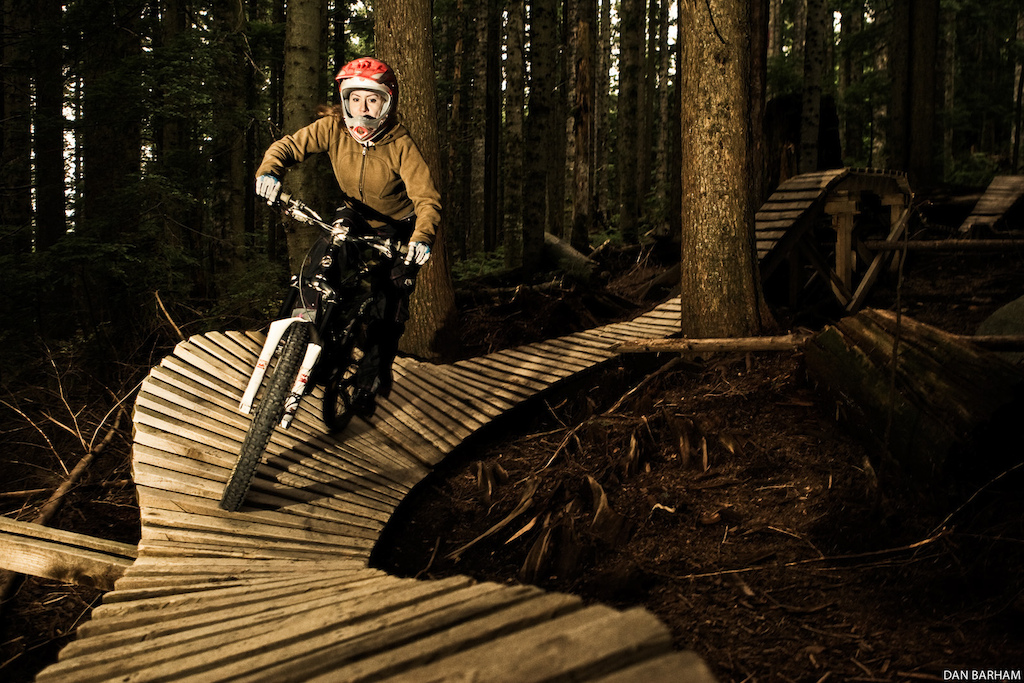 Sarah Fenton rides on the woodwork of mountain bike trail CBC on Mount Seymour North Vancouver BC Canada Photo Dan Barham