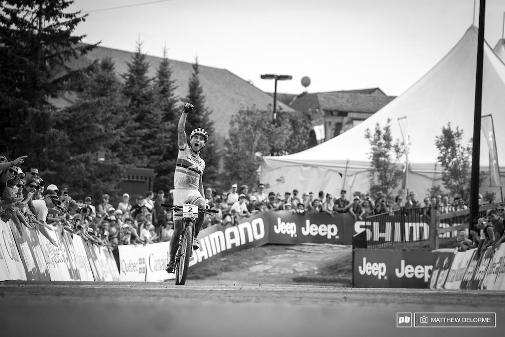 A triumphant Nino Schurter pumps his fist as he comes across the line.