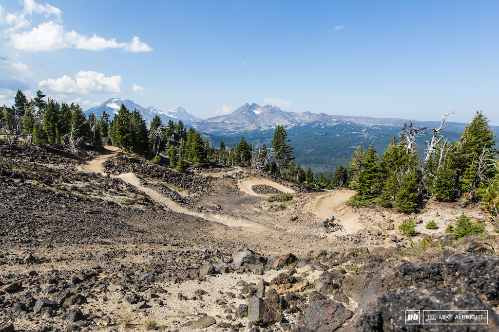 Lev Stryker and Henry Abel enjoy cruising on their Calfee MTB tandem on the Upper Lava Flow trail at Mt Bachelor Bike Park with the Three Sisters and Brokentop mountains in the background