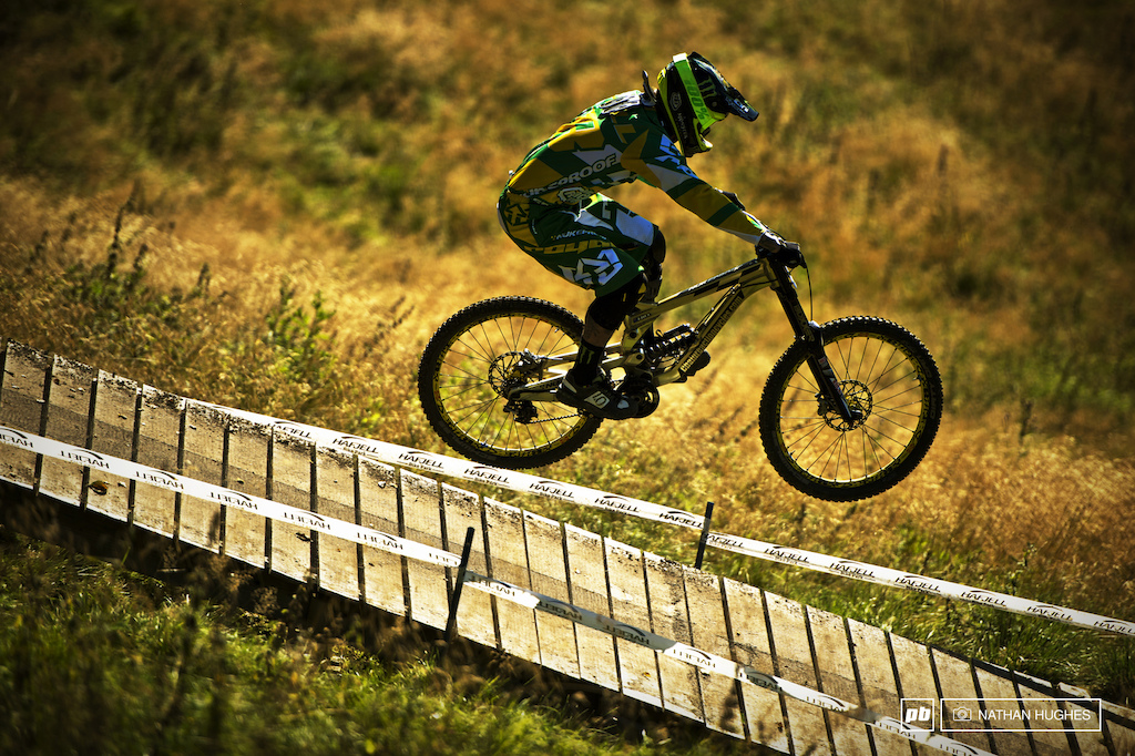 The gold and green figure and bike of Sam Hill camouflaging itself perfectly into the gold and green of the Hafjell terrain on the last run of practice.