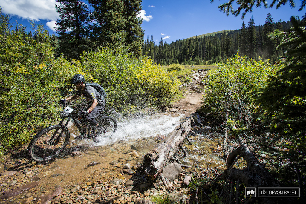 Will Olson smashes through one of many stream crossings on the open stage of five days of racing.
