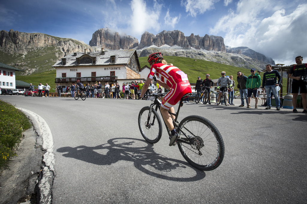 Perfect spot for spectators Annika Langvad on her way to Passo Pordoi . In the back the scenic rock towers of the Sella .