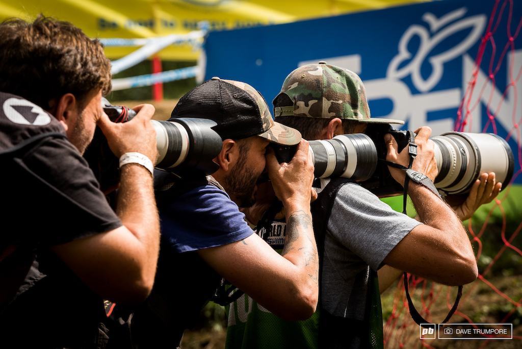 A 700mm lens held up by three of the sports finest photographers in the final corner.