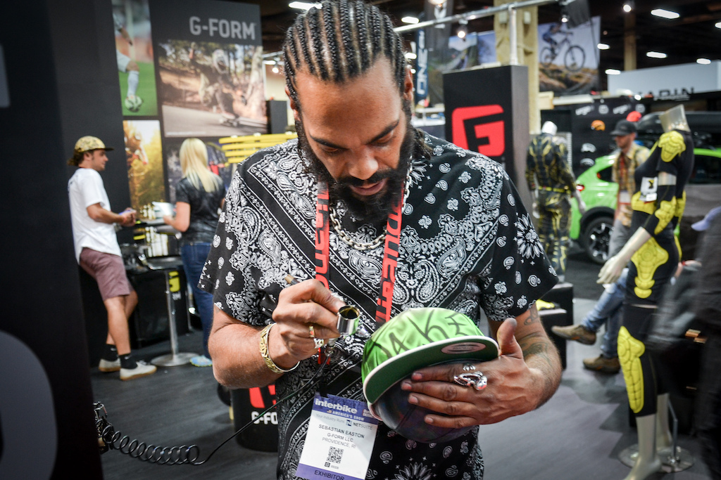 This guys was custom spray painting hats at the G-Form Booth.